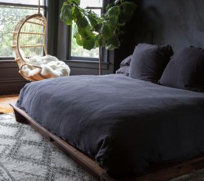Een donkere slaapkamer met een zwart dekbedovertrek