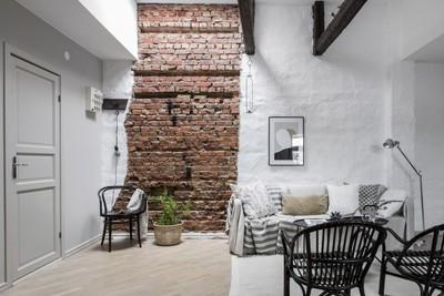 Binnenkijken in dit witte interieur met bakstenen muur